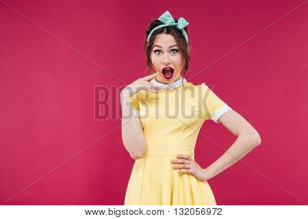 Surprised beautiful pinup girl in yellow dress standing with mouth opened over pink background