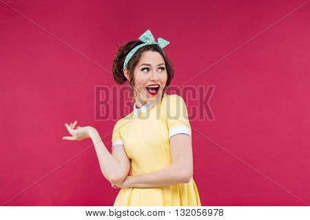 Cheerful playful pinup girl in yellow dress smiling and pointing away over pink background