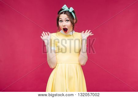 Surprised lovely pinup girl with mouth opened standing over pink background