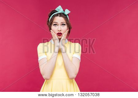 Sad shocked pretty pinup girl in yellow dress with hands on cheeks over pink background