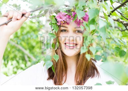 Young beautiful girl in the field with flowers in hair