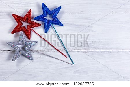 Colorful stars on rustic white wooden boards. Fourth of July holiday concept for United States of America.