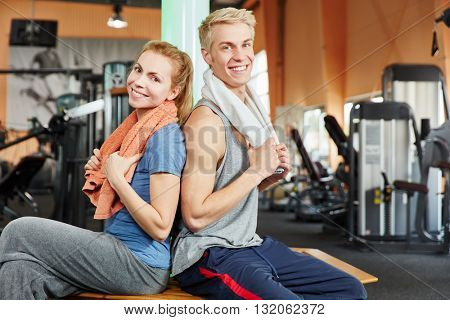 Man and woman smiling happily after workout at fitness studio