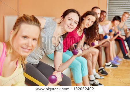 Women making exercise with weights during fitness class at the gym