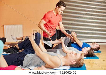 Coach motivating his pilates group with healthy stretching