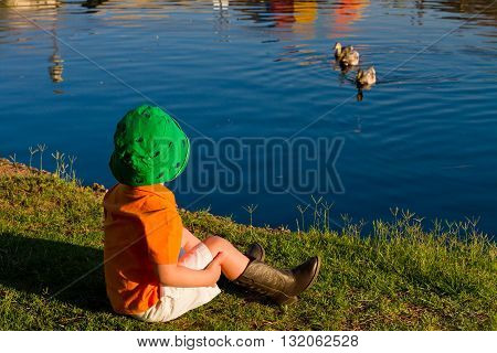 A small boy wearing cowboy boots and a fisherman's hat sits by a lake watching ducks who are also watching him.