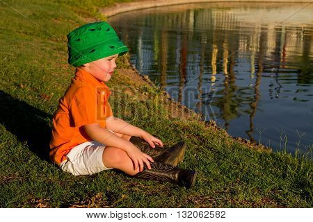 A little boy with a fisherman's hat and cowboy boots sits by a lake in the late afternoon sun.