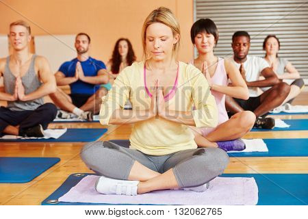 Group meditating together in yoga class at fitness center