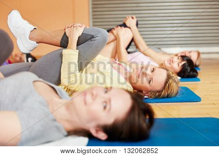 Group of women making gymnastics exercise during pilates class