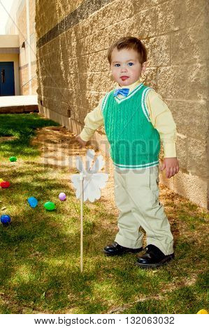 A little boy dressed in his best on Easter looks at the camera with a messy face.