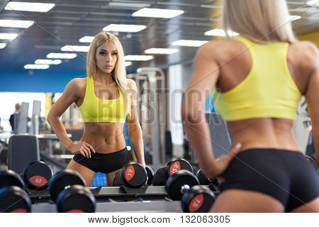 Blonde woman doing a workout with dumbbells in the gym