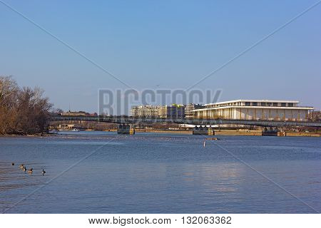 A view on John F. Kennedy Center for the Performing Arts in US capital from the Potomac River bank. Spring birds' migration on Potomac River in Washington DC.