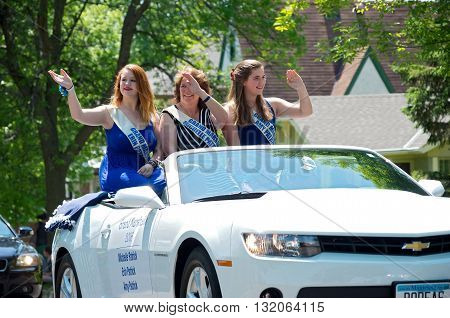 WEST ST. PAUL, MINNESOTA - MAY 21, 2016: Grand Marshalls of 2016 West St. Paul Days Grande Parade (from left to right) Erin Patrick, Michelle Patrick and Amy Patrick wave to crowd from car during parade in West St. Paul on May 21, 2016.