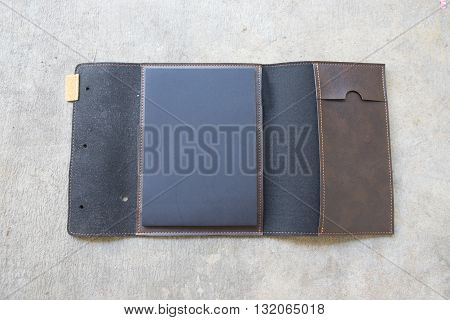 Black and brown leather cover notebook on stone