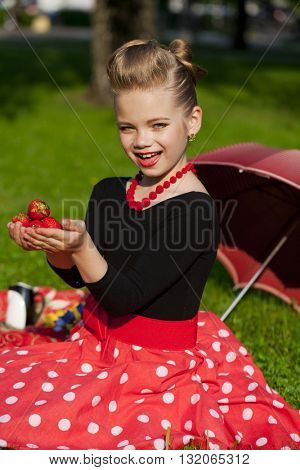Pin-Up. Lovely little girl in the retro red dress in summer park