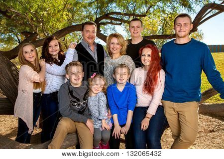 Portrait of a large family at the park under a tree. Parents with their eight children. Three brothers and fours sisters makes for lots of siblings.
