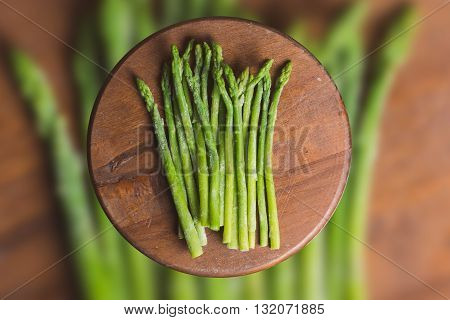 Frozen sticks of asparagus on rustic blurred wood and vegetable background. horizontal view
