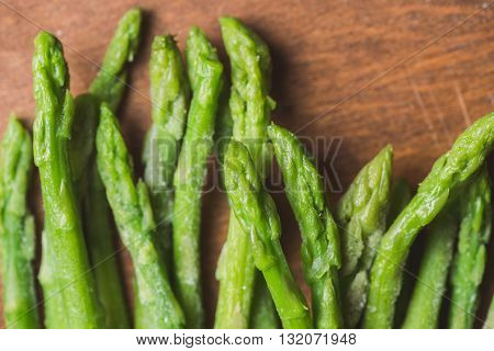Frozen sticks of asparagus on rustic wood background. horizontal view
