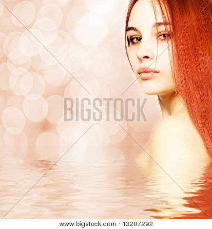 Beautiful redhead woman reflected in water