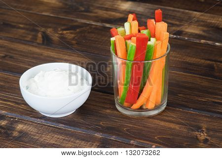 Colorful vegetable sticks in a glass and spicy white dip on wooden table