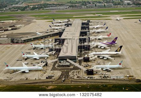 LONDON UK - MAY 30 2016: Aerial view of aeroplanes standing at Terminal 2 of London Heathrow Airport on a cloudy day in May. Airlines using this terminal include Air Canada Singapore Airlines and United Airlines.