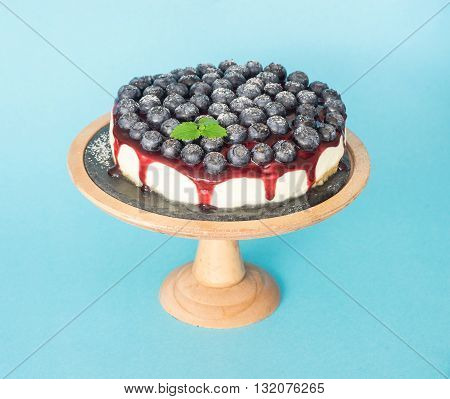 Cheesecake with a jam and blueberry on wooden stand and light blue background