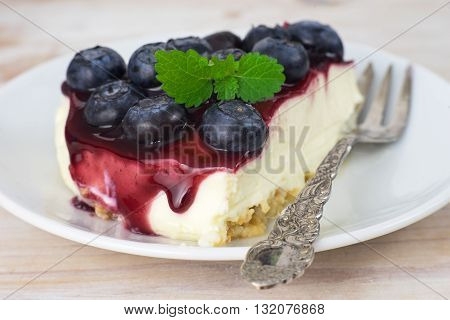 Close up of a peace of cheesecake with red jam, blueberry and mint on white plate with vintage fork