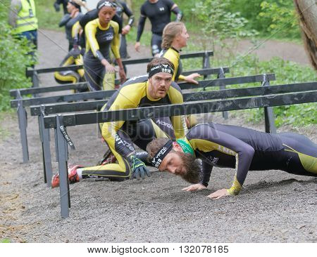STOCKHOLM SWEDEN - MAY 14 2016: Group of struggling people crawling under bars in the obstacle race Tough Viking Event in Sweden April 14 2016