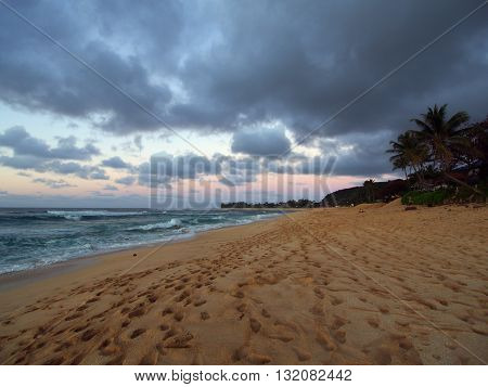 Foot prints cover the beach at Dusk on Sunset Beach on The North Shore with waves rolling in on Oahu Hawaii.