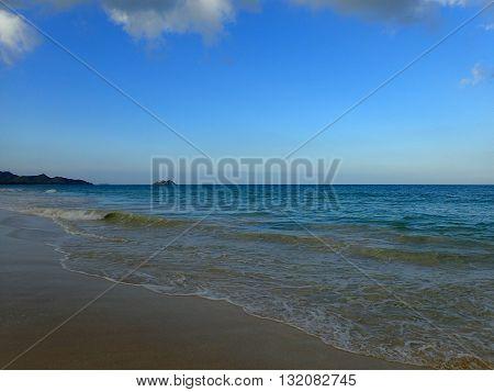 Waves lap on shore of Waimanalo Beach looking towards mokulua islands on Oahu Hawaii.