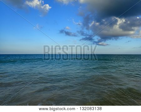 Shallow wavy ocean waters of Waimanalo bay looking into the pacific ocean with a clear blue sky on Oahu. poster