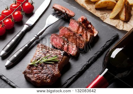 Grilled striploin sliced steak with potato and red wine over stone table