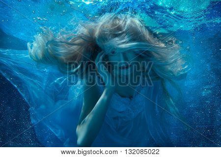 Fabulous blonde woman under water her long hair and a white dress.