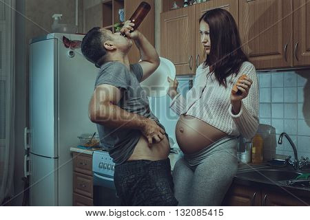 Husband in the kitchen drinking liquor his wife was afraid. Social problems of the family.