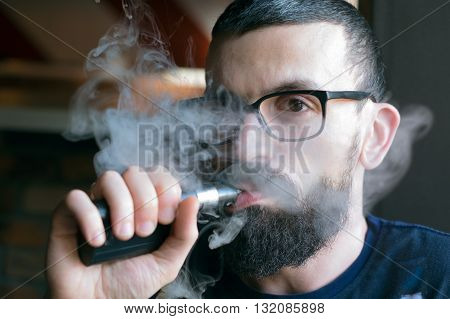 Bearded Man Smoking Vaporizer And Blows Smoke