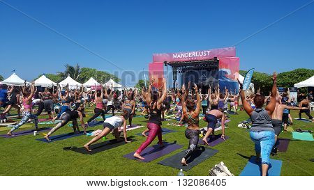 NORTH SHORE HAWAII - FEBRUARY 28: People raise arms over head in warrior one during outdoor yoga class facing stage at Wanderlust yoga event on the North Shore Hawaii on February 28 2016.