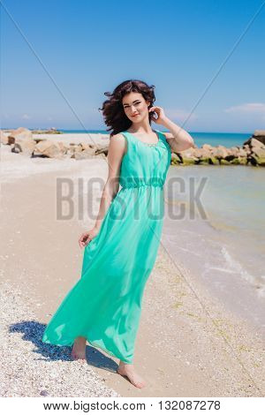 Young beautiful girl in a long dress on the beach in summer