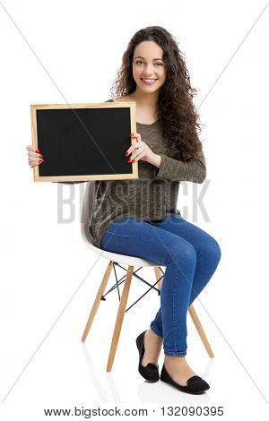 Beautiful and happy woman showing something on a chalkboard