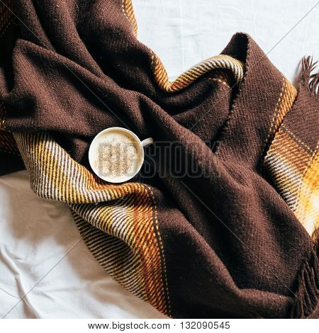 A cup of coffee in the morning wrapped in a brown blanket of wool on a white bed