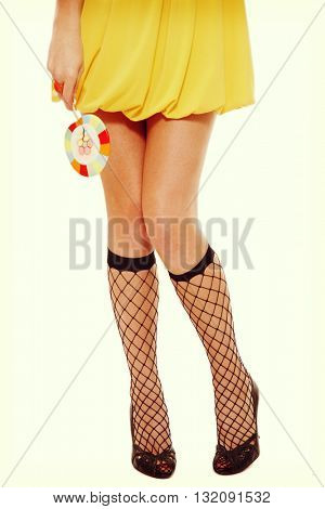 Vintage style shot of slim tanned legs of young sexy woman in fishnet knee socks and stilettos