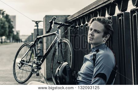 young man with a bicycle rests near the river