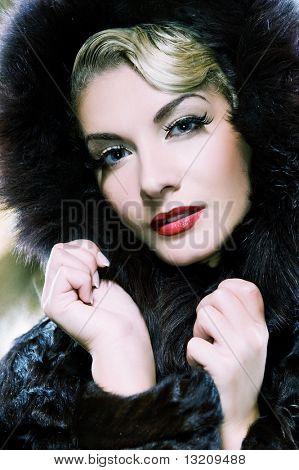 Beautiful woman in winter fur coat. Toned in blue