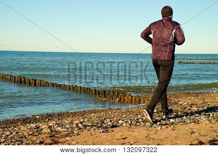 Man In Black Run  And Exercise On Beach At Breakwater.