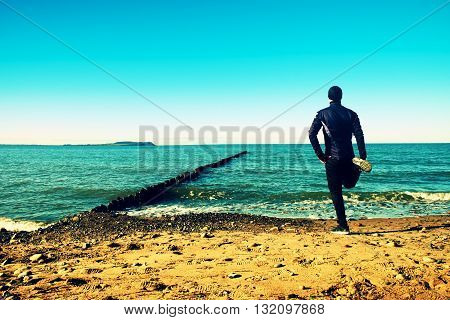 Tall Man In Black Suit Exercising On Stony Beach At Breakwater.