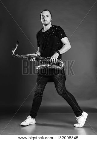 Young man playing saxophone. Man in modern clothes. Black and white photo.