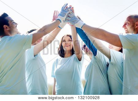 volunteering, charity, people, gesture and ecology concept - group of happy volunteers making high five in park