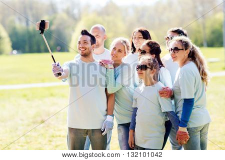 volunteering, charity, people, teamwork and environment concept - group of happy volunteers taking picture by smartphone and selfie stick in park