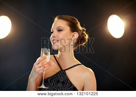 holidays, nightlife, drinks, people and luxury concept - beautiful young asian smiling woman drinking champagne at party over black background and spotlights