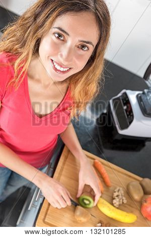Cacuasian happy smiling woman preparing smoothie with fresh fruits in the kitchen