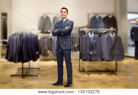 business, people, menswear, sale and clothes concept - happy smiling businessman in suit over clothing store background